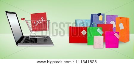 Trolley on laptop with sale bag against grey background