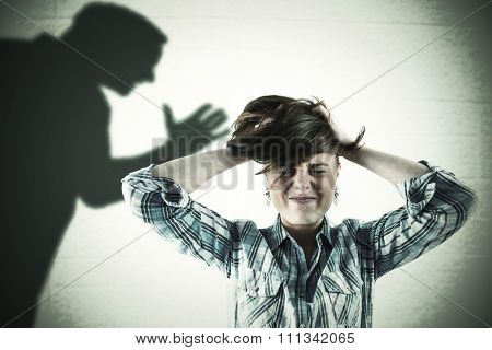 Pretty brunette getting a headache with hands on head against silhouette of man with raised hand
