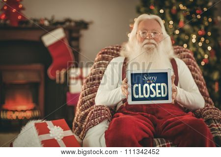 Vintage closed sign against santa claus showing tablets screen