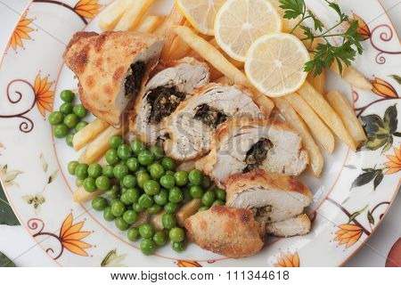 Chicken kiev with french fries and green peas