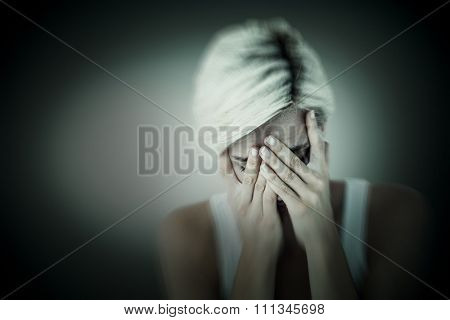 Sad blonde woman crying with head on hands against grey vignette