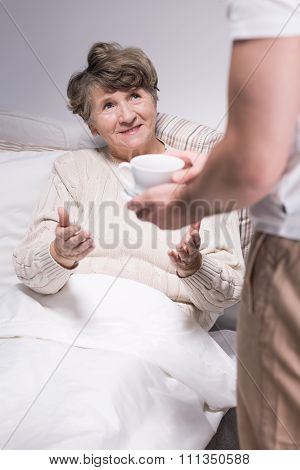 Male Carer Assisting Senior Woman