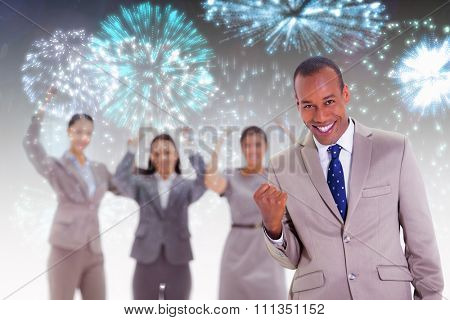 Successful business team with a man in the foreground against colourful fireworks exploding on black background