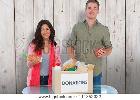 Smiling volunteers taking out food from donations box against wooden background