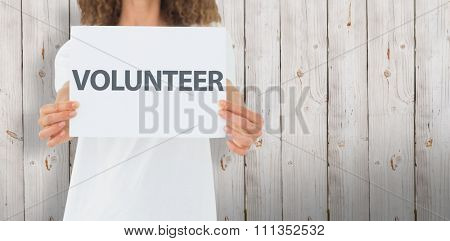 Volunteer showing a poster against wooden background