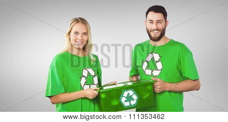 Portrait of smiling volunteers carrying recycling container against grey vignette