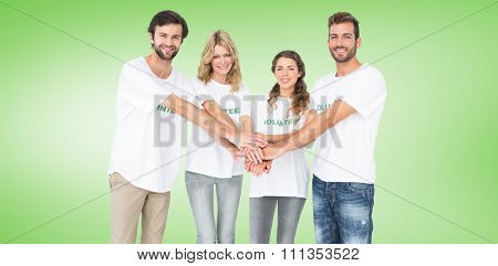 Group portrait of happy volunteers with hands together against green vignette