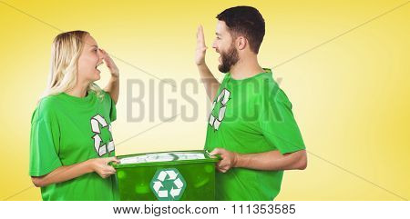 Smiling volunteer doing high five while holding container against yellow vignette