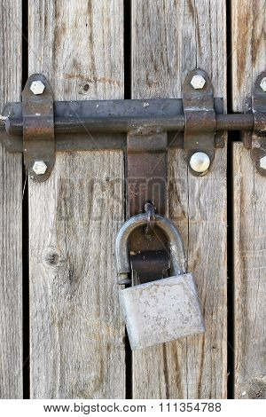 Padlock On Old Wooden Gate