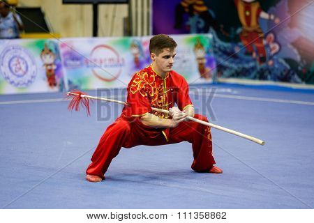JAKARTA, INDONESIA - NOVEMBER 17, 2015: Andrei Solovev of Russia performs the movements in the men's Qiangshu event at the 13th World Wushu Championship 2015 at the Istora Senayan Stadium.