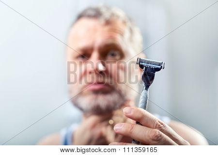 Man holds in his hand razor. Focus on razor