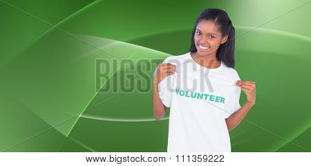 Young woman wearing volunteer tshirt and pointing to it against abstract green design