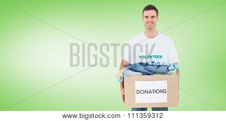 Attractive man holding donation box with clothes against green vignette