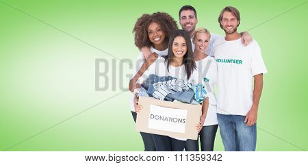 Smiling group of volunteers holding donation box against green vignette
