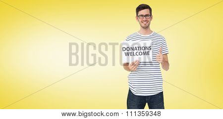 Man holding a donation welcome note while gesturing thumbs up against yellow vignette