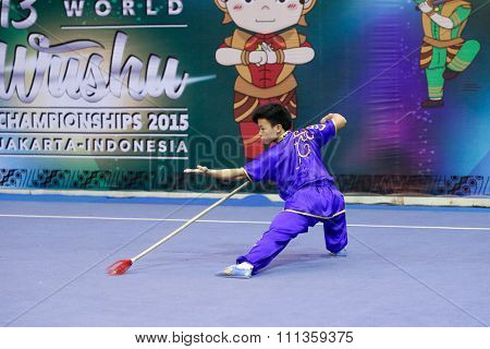 JAKARTA, INDONESIA - NOVEMBER 17, 2015: Chi Kuan Song of Macao performs the movements in the men's Qiangshu event at the 13th World Wushu Championship 2015 at the Istora Senayan Stadium.