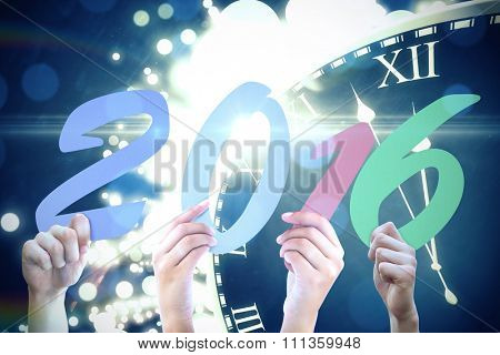 Hands showing 2016 against black and gold new year graphic