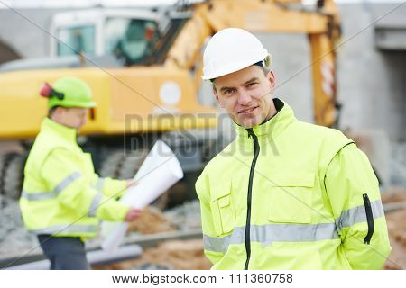 Portrait of engineer builder with colleague with blueprint plan at construction site with machinery