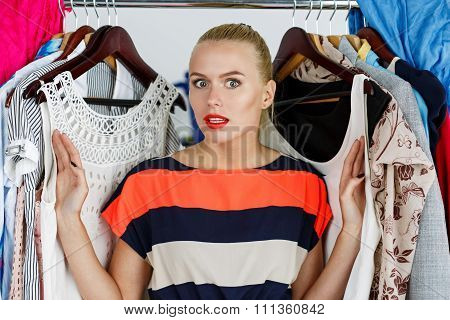 Beautiful Thoughtful Blonde Woman Standing Inside Wardrobe Rack Full Of Clothes