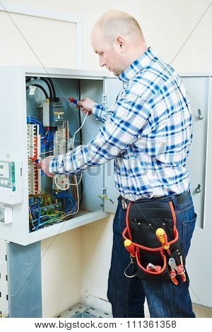 electrician measure high voltage with electrical tester meter in fuse box