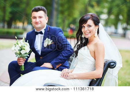 Wedding couple. Portrait of happy cheerful bride and  bridegroom with fresh flower bouquet sitting on bench outdoors in a park.