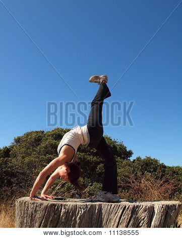 Attractive 20-something Lady Does A Backbend On Old Tree Stump While Lifting Leg
