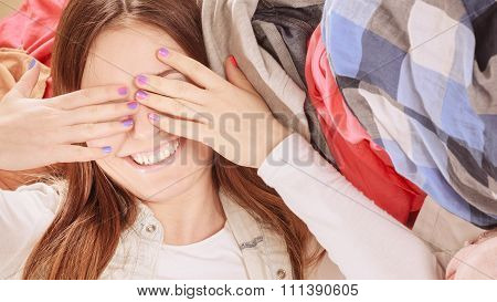 Happy Woman Lying On Clothes Covering Eyes.