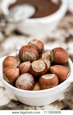 Chocolate Cream And Hazelnuts In White Bowls On Napkin