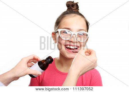 child is taking a drug administered on a spoon.