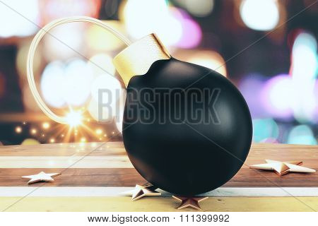 Christmass Black Small Bomb With A Lit Fuse And Golden Stars On Wooden Table