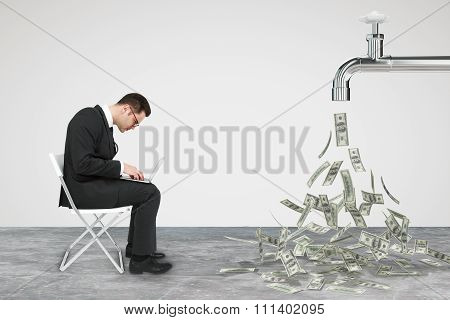 Businessman Working Opposite Flow Of Dollars From The Faucet Concept