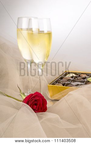 Two Glasses of Champagne, Single Red Rose and an Open Box of Gourmet Chocolates