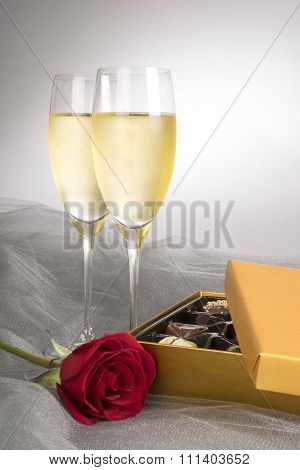 Two Glasses of Champagne with One Single Red Rose and Box of Gourmet Chocolates