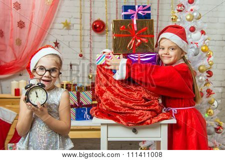 One Girl Keeps Watch Over Time, 11-55, Another In A Suit Of Santa Claus Hugging A Bag With Gifts