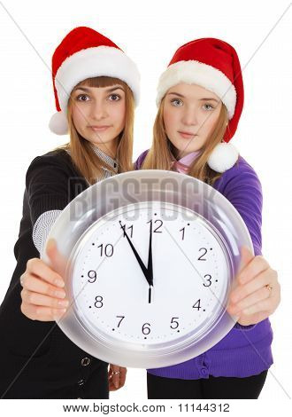 Two Girls In New Year's Caps With Clock