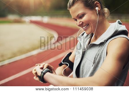 Fit Young Woman Looking At Her Watch While Standing On Track Field