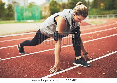 Young Sportswoman Stretching On Track Field