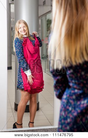 Woman trying red dress shopping for clothing.