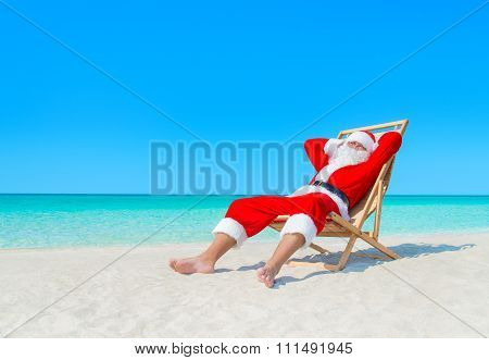 Christmas Santa Claus Resting On Deckchair At Ocean Tropical Beach