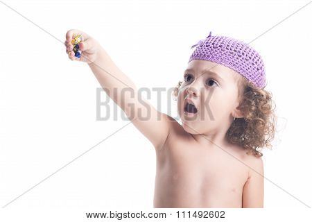 Child With Hat That Is Offering A Candy Paper