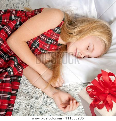 Little Girl Sleeping With Gift. Dreams Come True!