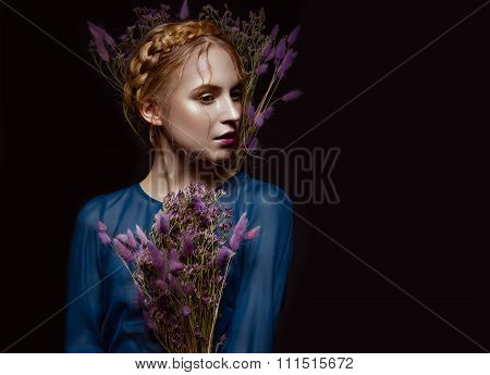 Beautiful girl with a gentle make-up, hairstyle  in the form of braids,  dry flowers, blue dress. Be