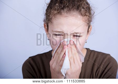 Little girl blows her nose with a napkin isolated over white.