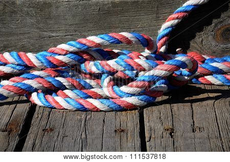 A piece of red, white and blue rope coiled on a dock