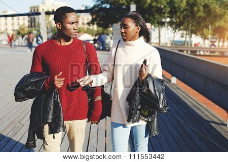 Two young man and woman students walking on a campus during break between lectures in University