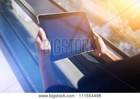 Female using digital tablet while standing near office window