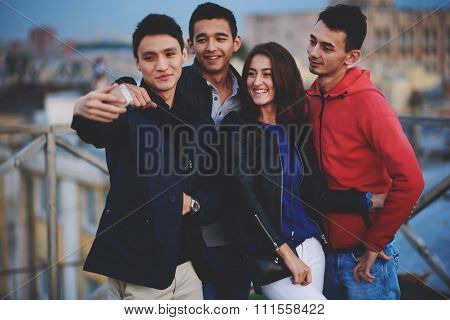 Stylish cheerful friends making self photo on cell telephone during walk