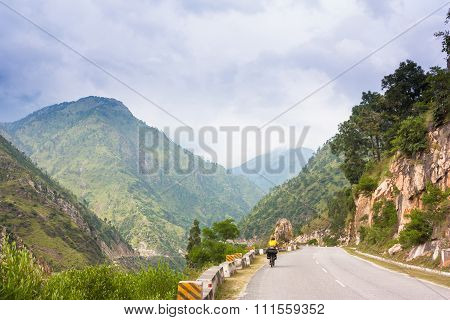 Himalayas landscape with two cyclist, mountains, road, river and clouds