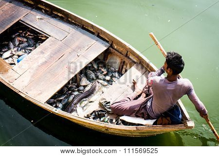 Man on wooden boat fishing in jaipur