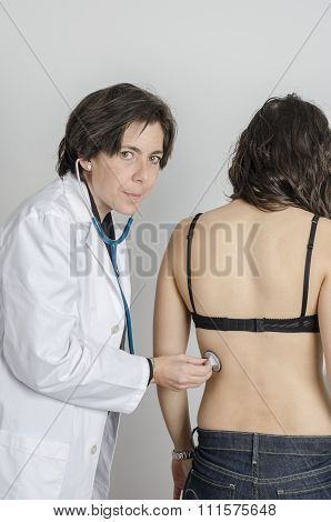 Doctor Female Auscultating Young Patient By Stethoscope.